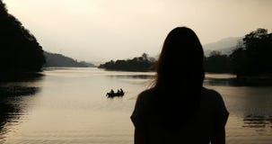 一个女孩的剪影湖和小船背景的  股票视频
