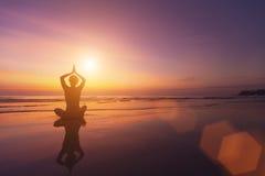 一个女孩的剪影瑜伽姿势的在美好的日落的由海 放松 免版税库存照片