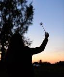 一个女孩的剪影用在日落背景的蒲公英 库存图片