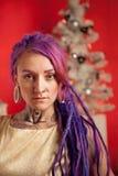一个女孩的圣诞节照片有紫色dreadlocks和纹身花刺的在演播室 免版税图库摄影