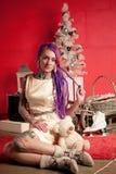 一个女孩的圣诞节照片有紫色dreadlocks和纹身花刺的在演播室 免版税库存照片