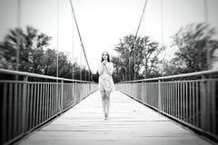 一个女孩的情感画象一座下垂桥梁的 一个女孩在su 库存照片
