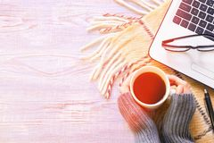 一个女孩的手拿着咖啡杯的一件温暖的灰色毛线衣的在膝上型计算机的工作 免版税库存图片