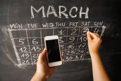 一个女孩的手有一个智能手机的在一个黑暗的黑板的墙壁写的日历的背景 免版税库存图片