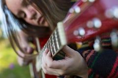 一个女孩的手特写镜头弹声学吉他的 业余爱好 免版税库存照片