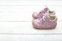 一个女孩的桃红色小的鞋子白色木背景的 免版税库存图片