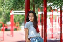 一个女孩的特写镜头便衣的在被弄脏的赛场背景 时尚,都市,青年概念 复制空间 免版税库存照片