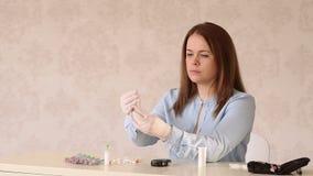 一个女孩的特写镜头医疗手套的打开一个不育的瓶胰岛素 影视素材
