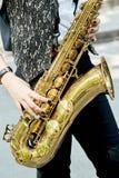 一个女孩的特写镜头有一支美丽的金黄萨克斯管的 免版税图库摄影