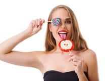 一个女孩的特写镜头有棒棒糖的用不同的形状,隔绝在白色背景 免版税库存图片