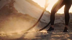 一个女孩的特写镜头有绳索的在海滩附近举办在含沙地面上的室外训练 绳索在妇女的手上 股票录像
