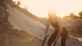 一个女孩的特写镜头有绳索的在海滩附近举办在含沙地面上的室外训练 绳索在妇女的手上 股票视频