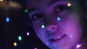 一个女孩的特写镜头面孔通过光亮光 影视素材