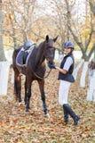 一个女孩的特写镜头,有一匹马的在步行的公园,拿着辔马 库存照片