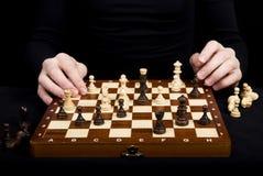 一个女孩的特写镜头手一个木棋盘的有棋figu的 免版税库存照片