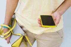 一个女孩的特写镜头有一个黄色手机和女性袋子的 库存照片