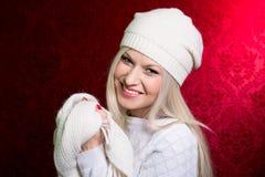 一个女孩的特写镜头画象一件白色盖帽和毛线衣的 免版税库存照片