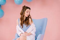 一个女孩的画象一件蓝色礼服的在一间桃红色屋子 图库摄影
