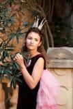 一个女孩的画象一位公主的一件神仙的服装礼服的在一座古老城堡的庭院里 库存图片