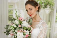 一个女孩的画象一根白色鞋带的与花束 白色长袍,便服 用hairdress小圆面包 免版税图库摄影
