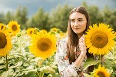 一个女孩的画象以开花的向日葵为背景的 免版税库存照片