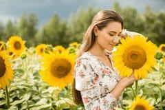 一个女孩的画象以开花的向日葵为背景的 库存图片