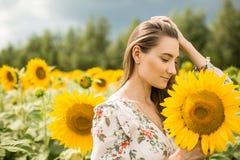 一个女孩的画象以开花的向日葵为背景的 免版税库存图片