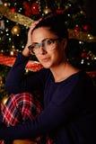 一个女孩的画象在圣诞树前面的 免版税库存照片