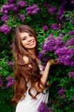 一个女孩的画象在春天在一个开花的庭院里 免版税库存图片
