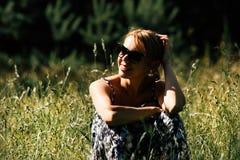 一个女孩的画象太阳镜的在草甸 库存照片