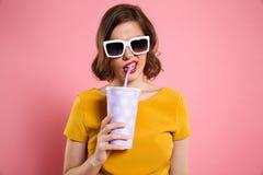 一个女孩的画象拿着有饮料的太阳镜的杯子 免版税库存照片