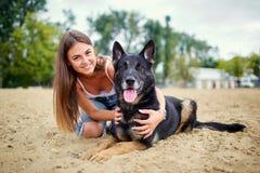 一个女孩的画象有一条狗的由一只德国牧羊犬 免版税库存图片
