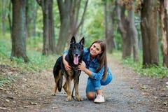一个女孩的画象有一条狗的由一只德国牧羊犬 库存图片