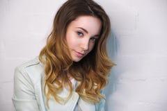 一个女孩的画象有流动的假发的和在照相机的悦人的神色在白色背景 图库摄影