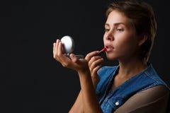 一个女孩的画象绘她的有红色唇膏的嘴唇的黑背景的 免版税库存图片