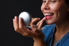 一个女孩的画象绘她的有红色唇膏的嘴唇的黑背景的 免版税库存照片