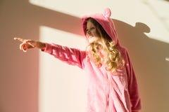 一个女孩的画象软绵绵地温暖的桃红色睡衣的 女孩7岁,白肤金发与长的卷发,在敞篷,看  免版税库存照片