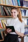一个女孩的画象,有一本书的在图书馆里 免版税图库摄影