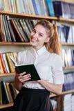 一个女孩的画象,有一本书的在图书馆里 免版税库存图片