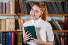 一个女孩的画象,有一本书的在图书馆里 免版税库存照片