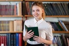 一个女孩的画象,有一本书的在图书馆里 库存照片