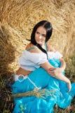 一个女孩的纵向在干草堆旁边的 库存照片