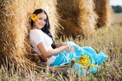 一个女孩的纵向在干草堆旁边的 免版税图库摄影