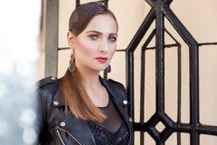 一个女孩的美丽的射击有明亮的时髦构成的在仿照迷人的岩石样式的黑皮革裙子 图库摄影