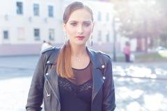 一个女孩的美丽的射击有明亮的时髦构成的在黑皮革裙子在迷人石样式luchas阳光下在日落 免版税库存照片