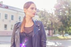 一个女孩的美丽的射击有明亮的时髦构成的在黑皮革裙子在迷人石样式luchas阳光下在日落 库存图片