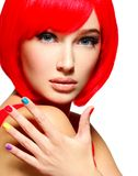 一个女孩的美丽的面孔有时髦的多色钉子的 免版税库存照片