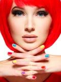 一个女孩的美丽的面孔有时髦的多色钉子的 库存照片