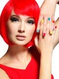 一个女孩的美丽的面孔有时髦的多色钉子的 免版税库存图片