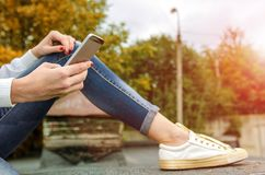 一个女孩的腿和手有电话的在公园 库存图片